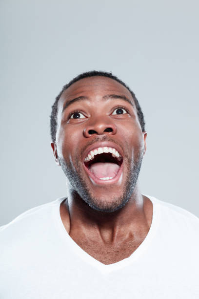 Excited afro american man looking away and laughing Close up portrait of excited young afro american man looking away and laughing against gray background mouth open stock pictures, royalty-free photos & images