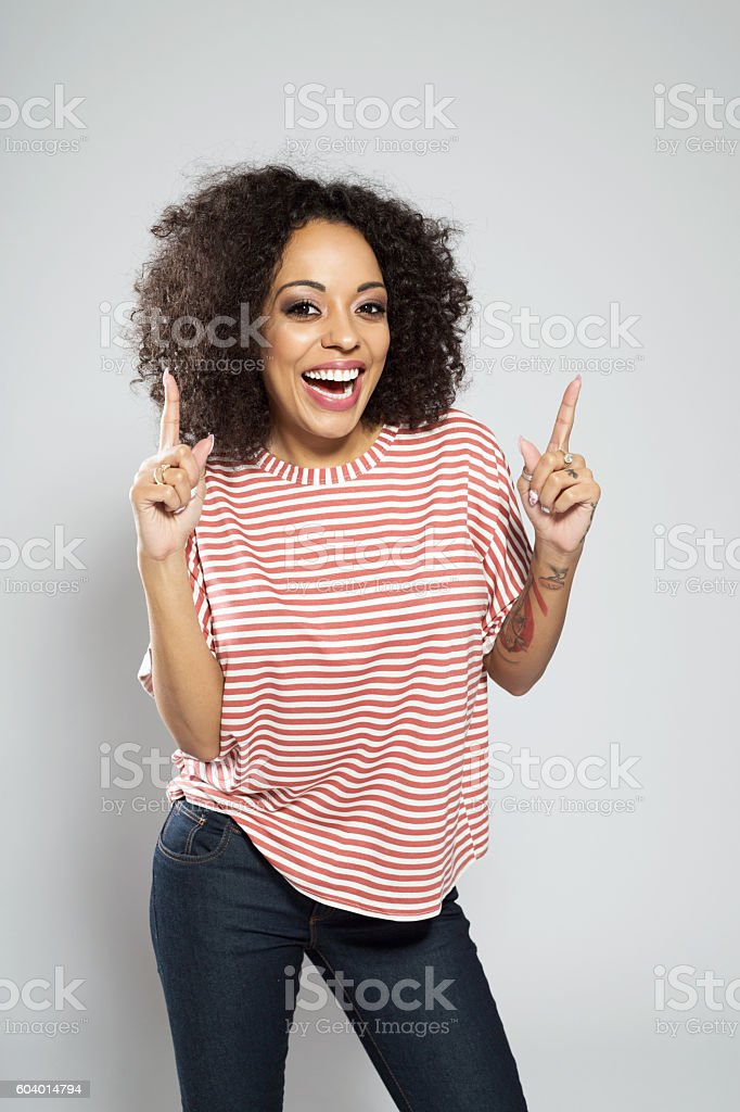 Excited afro american woman pointing at copy space Portrait of excited afro american young woman wearing striped top, standing against grey background and pointing with index fingers at the copy space. Adult Stock Photo