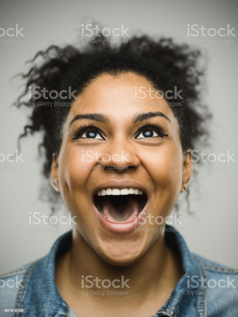 Excited afro american woman shouting against gray background stock photo