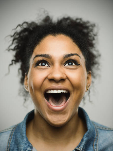 Excited afro american woman shouting against gray background Close-up portrait of a real happy young afro american woman shouting and looking up. Cheerful female is against gray background. Vertical studio photography from a DSLR camera. Sharp focus on eyes. mouth open stock pictures, royalty-free photos & images