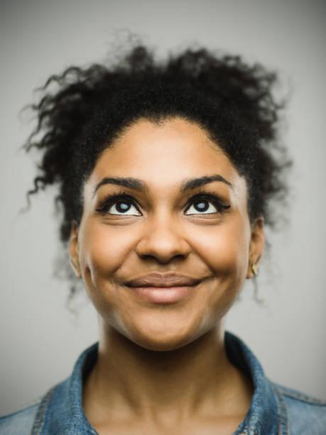 aufgeregt afro amerikanische frau lächelnd vor grauem hintergrund - serien schauen stock-fotos und bilder