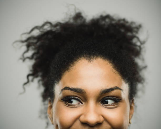 Excited afro american woman smiling against gray background stock photo