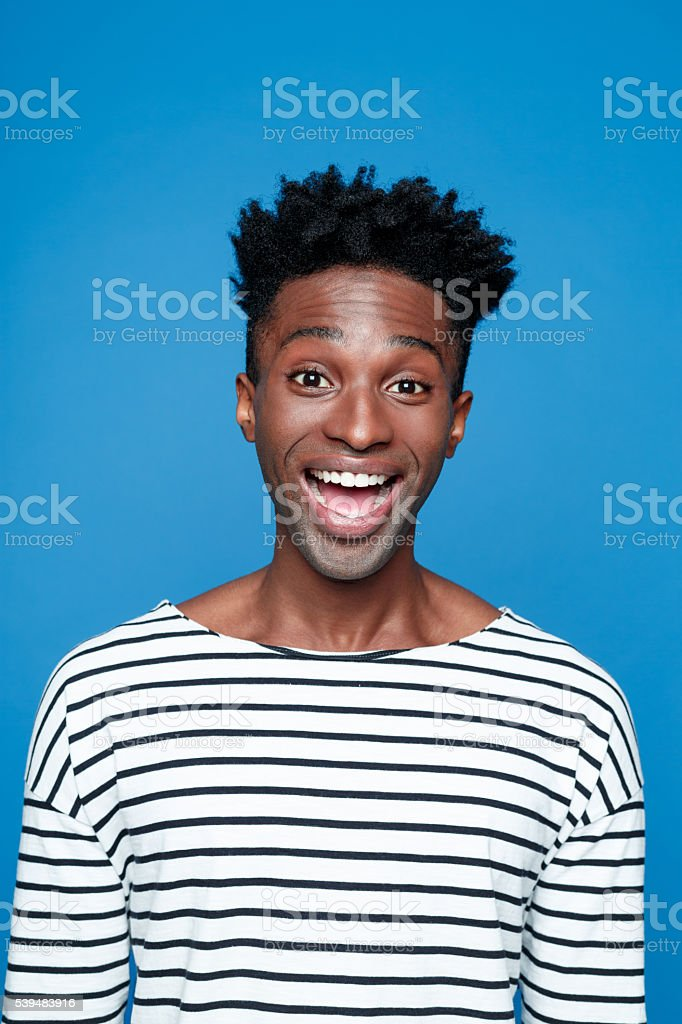 Excited afro american young man Portrait of happy afro american guy wearing striped long sleeved t-shirt, staring at camera with mouth open, raising eyebrows. Studio shot, blue background.  Adult Stock Photo