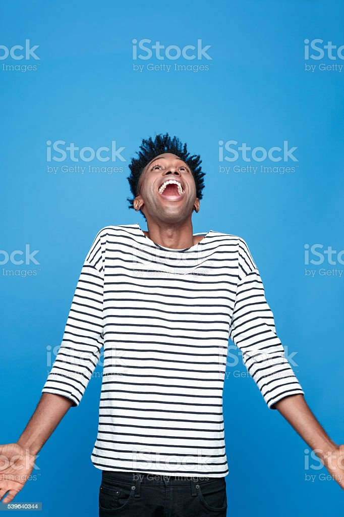 Excited afro american young man Portrait of happy afro american guy wearing striped long sleeved t-shirt, looking up and laughing. Studio shot, blue background.  Adult Stock Photo