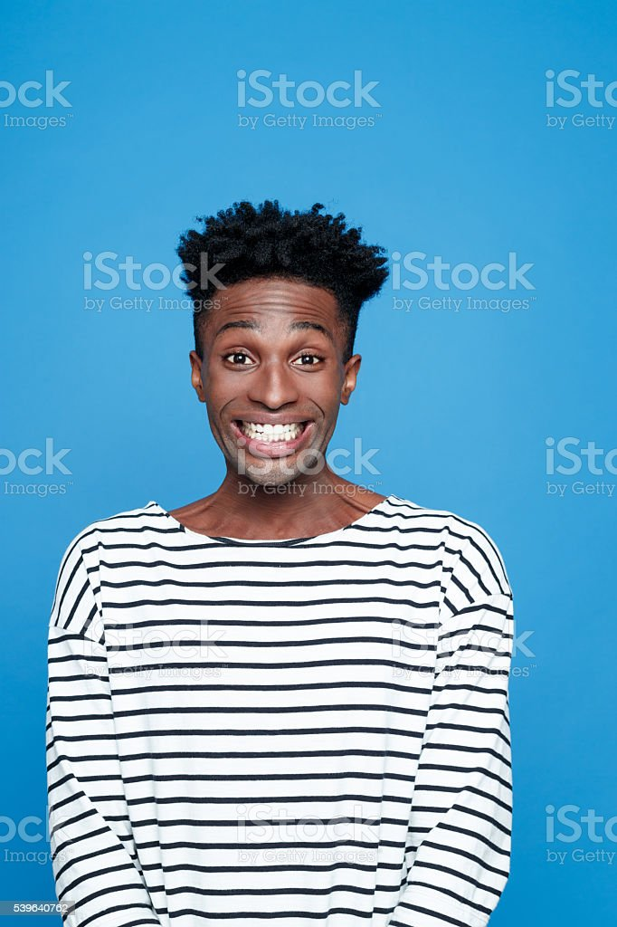 Excited afro american young man Portrait of happy afro american guy wearing striped long sleeved t-shirt, staring at camera. rolling eyes, raising eyebrows. Studio shot, blue background.  Adult Stock Photo