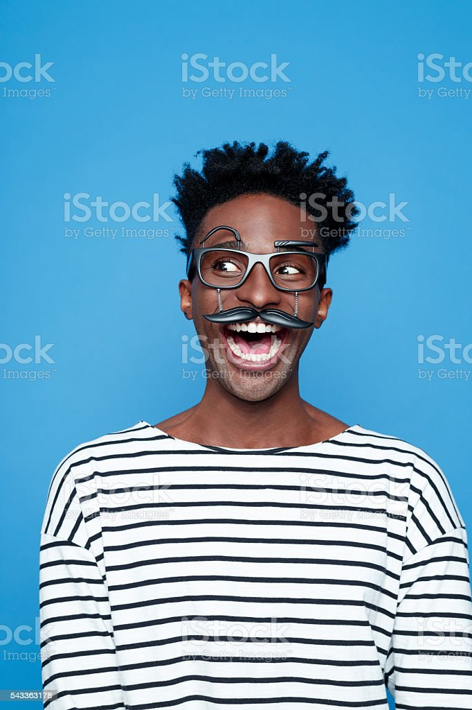 Excited afro american young man wearing funny glasses Portrait of excited afro american guy wearing striped long sleeved t-shirt and funny glasses, laughing. Studio shot, blue background.  Adult Stock Photo
