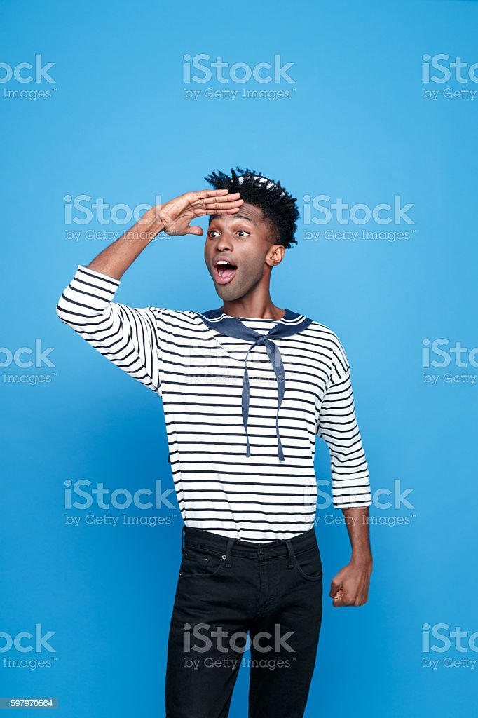 Excited afro american young sailor looking away Portrait of excited afro american young man in sailor style outfit, looking away withe raised hand and mouth open. Studio portrait, blue background. Adult Stock Photo