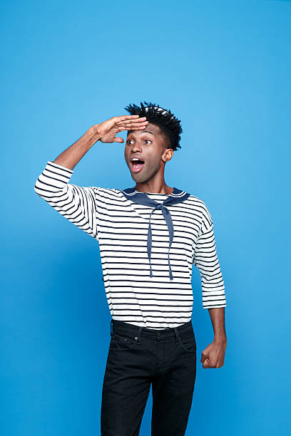Excited afro american young sailor looking away Portrait of excited afro american young man in sailor style outfit, looking away withe raised hand and mouth open. Studio portrait, blue background. sailor suit stock pictures, royalty-free photos & images