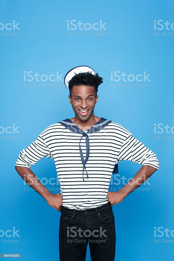 Excited afro american young sailor Portrait of happy afro american young man in sailor style outfit, smiling at camera with hands on hips. Studio portrait, blue background. Adult Stock Photo