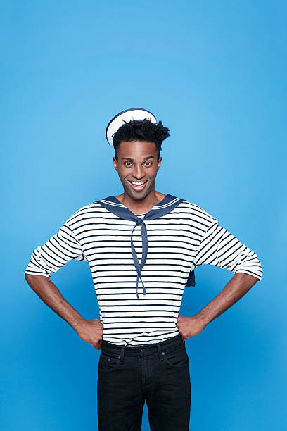 Excited afro american young sailor Portrait of happy afro american young man in sailor style outfit, smiling at camera with hands on hips. Studio portrait, blue background. sailor suit stock pictures, royalty-free photos & images