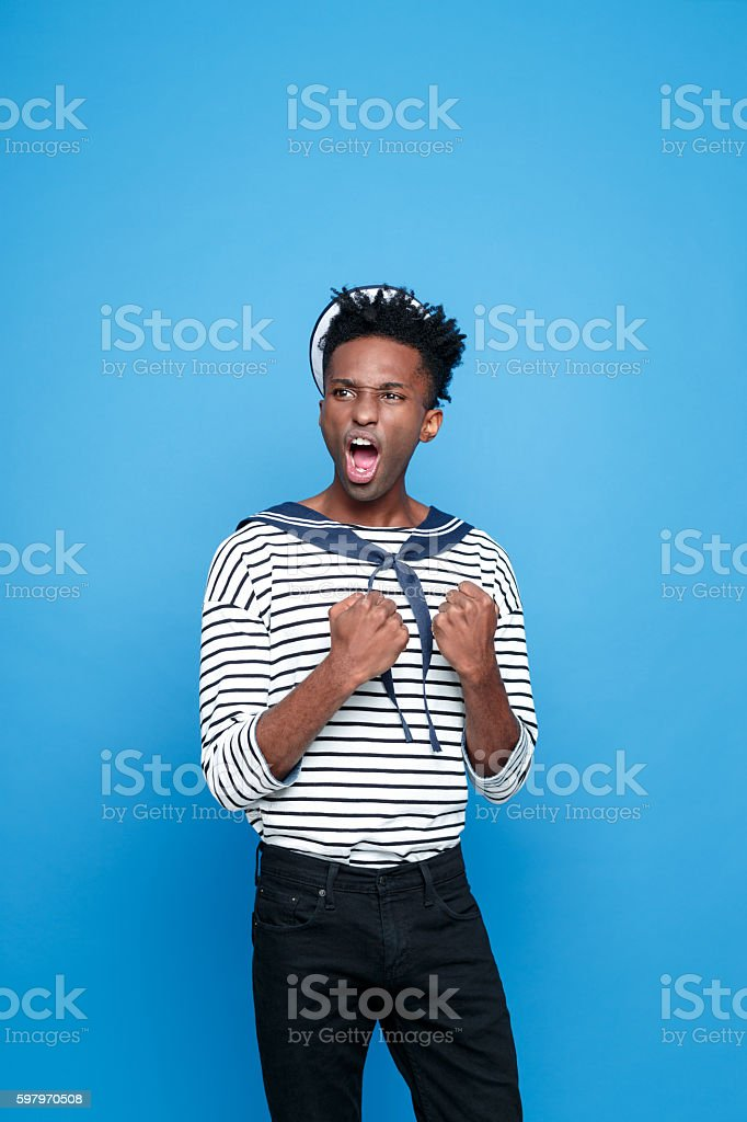 Excited afro american young sailor screaming Portrait of excited afro american young man in sailor style outfit, screaming. Studio portrait, blue background. Adult Stock Photo
