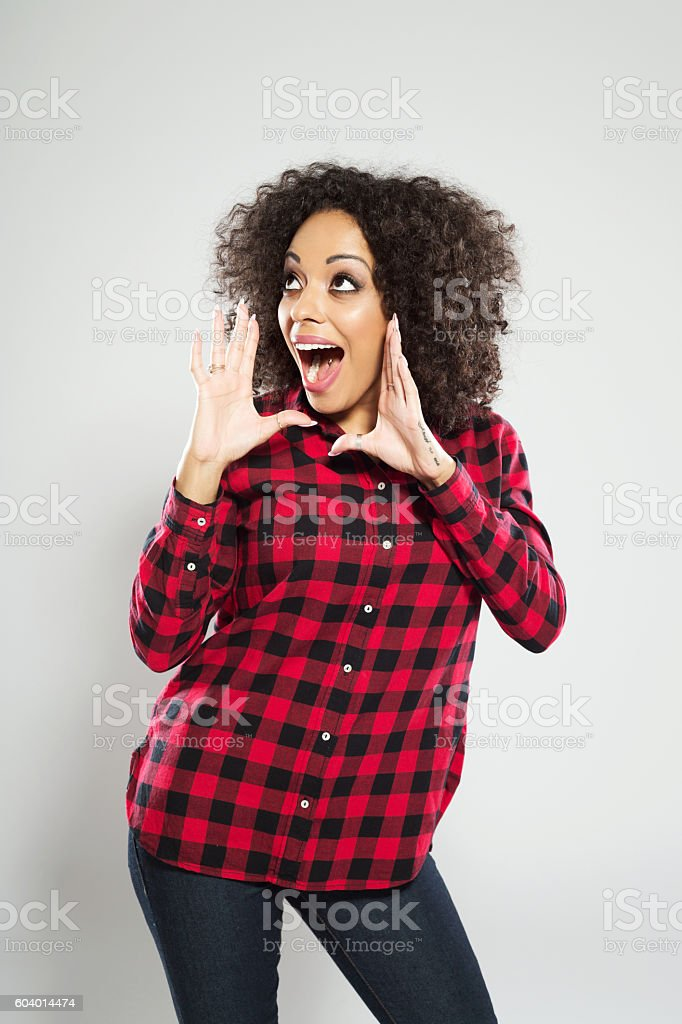 Excited afro american young woman shouting Portrait of excited afro american young woman wearing casual checkered dress, standing against grey background and shouting. Adult Stock Photo