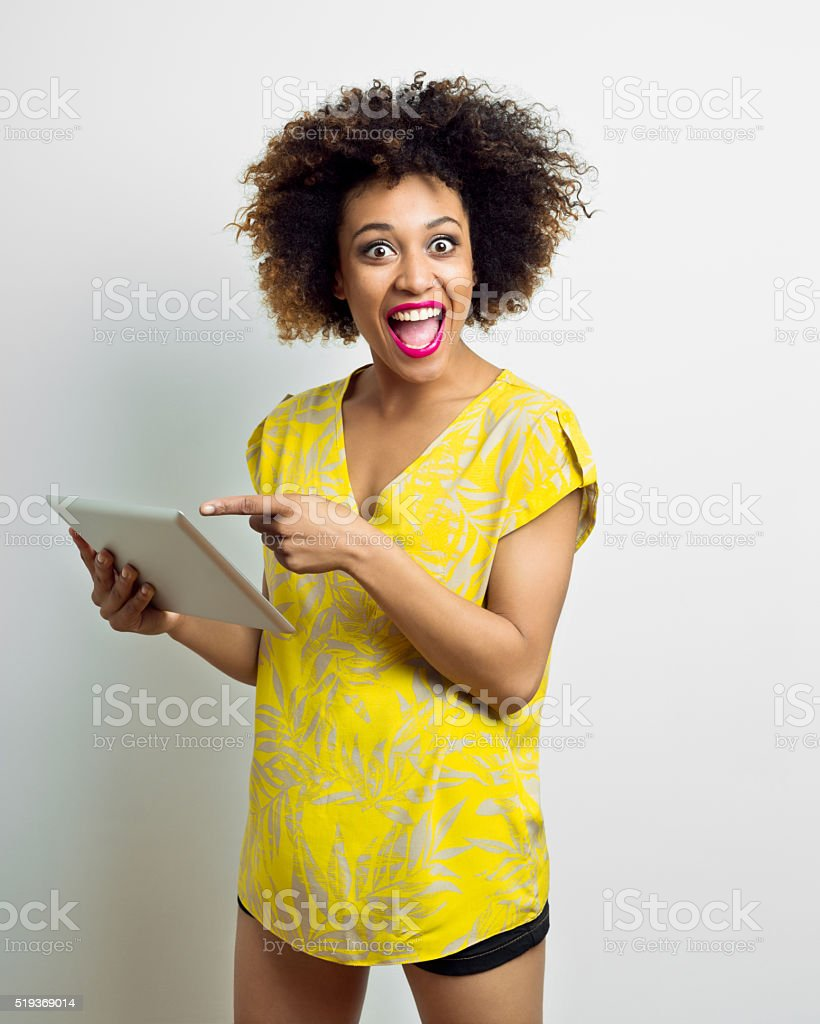 Excited afro american young woman using a digital tablet stock photo
