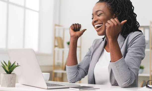 Excited Afro Businesswoman Celebrating Success At Work Business Success. African American Businesswoman Celebrating Victory At Work. Free Space excited stock pictures, royalty-free photos & images