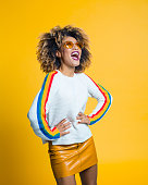 istock Excited afro girl standing against yellow background 1094454170