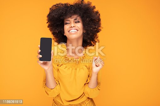 1159261513 istock photo Excited afro girl with mobile phone. 1159261513