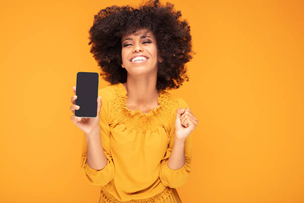 opgewonden afro meisje met mobiele telefoon. - tonen stockfoto's en -beelden