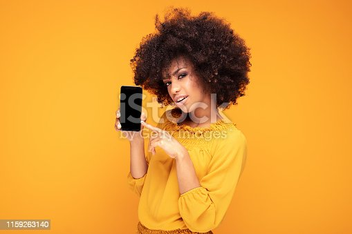 1159261513 istock photo Excited afro girl with mobile phone. 1159263140