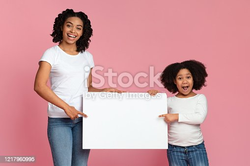 1159989540 istock photo Excited Afro mother and daughter holding and pointing at white placard 1217960995