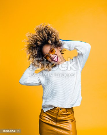 Happy and energetic afro young woman dancing against yellow background. Studio shot.