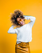 istock Excited afro young woman dancing against yellow background 1094454112