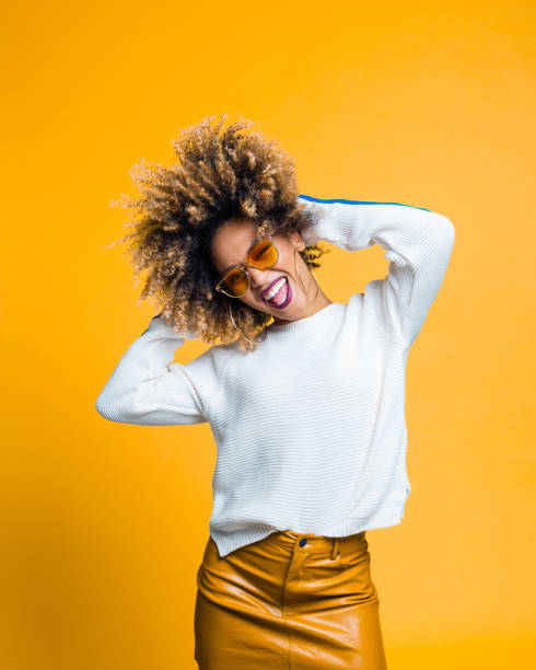 excited afro young woman dancing against yellow background - funky stock pictures, royalty-free photos & images