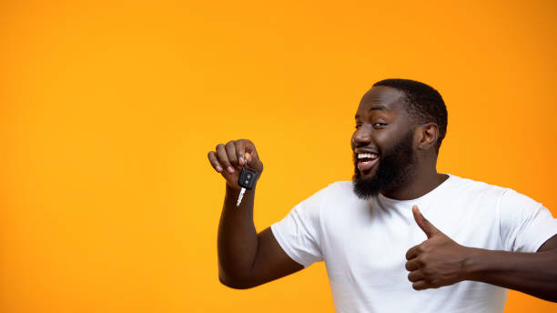 Excited Afro-American man holding car key and showing thumbs up, purchase Excited Afro-American man holding car key and showing thumbs up, purchase car key stock pictures, royalty-free photos & images