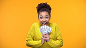 istock Excited Afro-American woman holding bunch of dollars, lottery winner, fortune 1142207897
