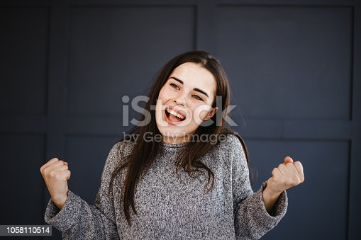 1045527172 istock photo Excited agitated euphoric woman make win gesture 1058110514