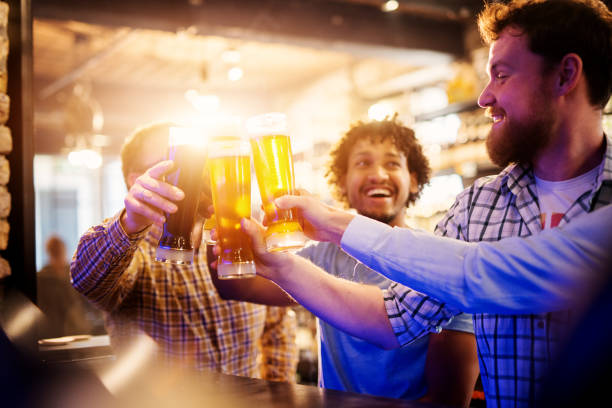 Excited american friends clinking with draft beer and celebrating the end of the week. stock photo