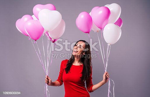 579443552istockphoto Excited and happy elegand young woman in red holds in hands many colorful balloons isolated in studio 1093600034