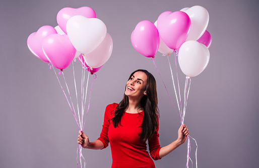 579443552 istock photo Excited and happy elegand young woman in red holds in hands many colorful balloons isolated in studio 1093600034