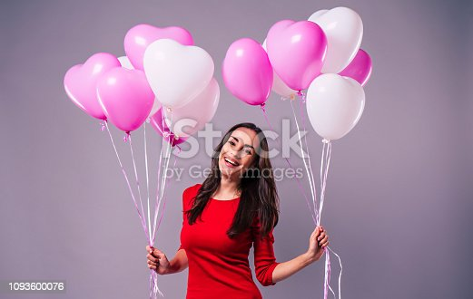 579443552istockphoto Excited and happy elegand young woman in red holds in hands many colorful balloons isolated in studio 1093600076
