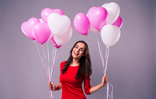 579443552 istock photo Excited and happy elegand young woman in red holds in hands many colorful balloons isolated in studio 1093600076