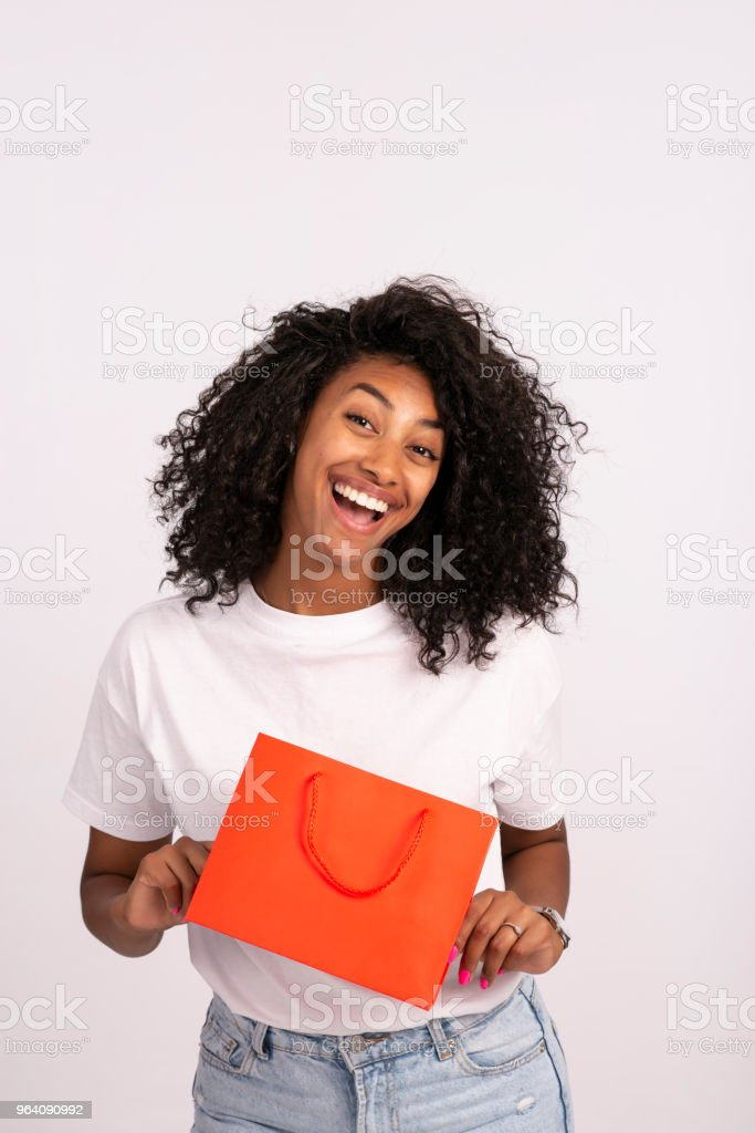 興奮と笑みを浮かべて美しい若い女性赤いショッピング バッグを保持しています。 - 1人のロイヤリティフリーストックフォト