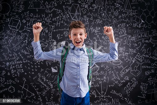 istock Excited and victorious boy against blackboard with mathematical 519656356