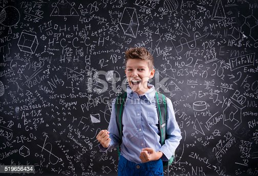 istock Excited and victorious boy against blackboard with mathematical 519656434