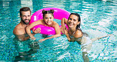 istock Excited and young happy family on vacation in the spa hotel are relaxing and have fun in the swimming pool. Summer rest 1263551842