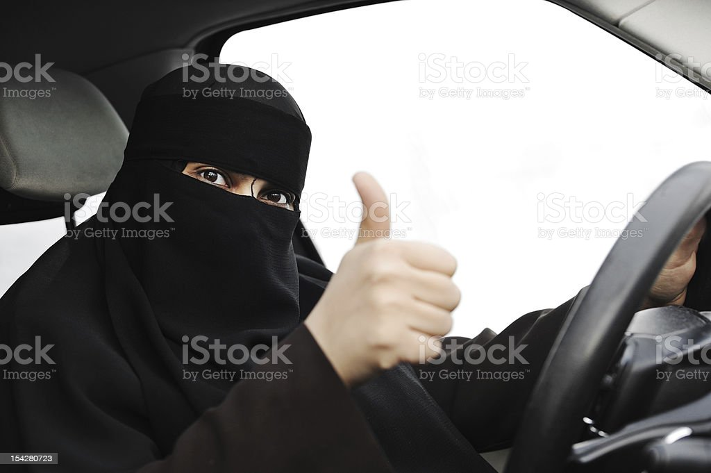 Excited Arabic Muslim woman with veil and scarf  driving car stock photo