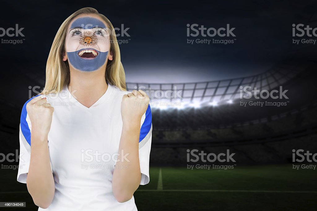 Excited argentina fan in face paint cheering stock photo