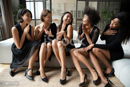 Happy excited Asian girl show praise diamond ring to multiracial friends girls at bridal shower, overjoyed bride and bridesmaids wear black dresses celebrate bachelorette night hen party together