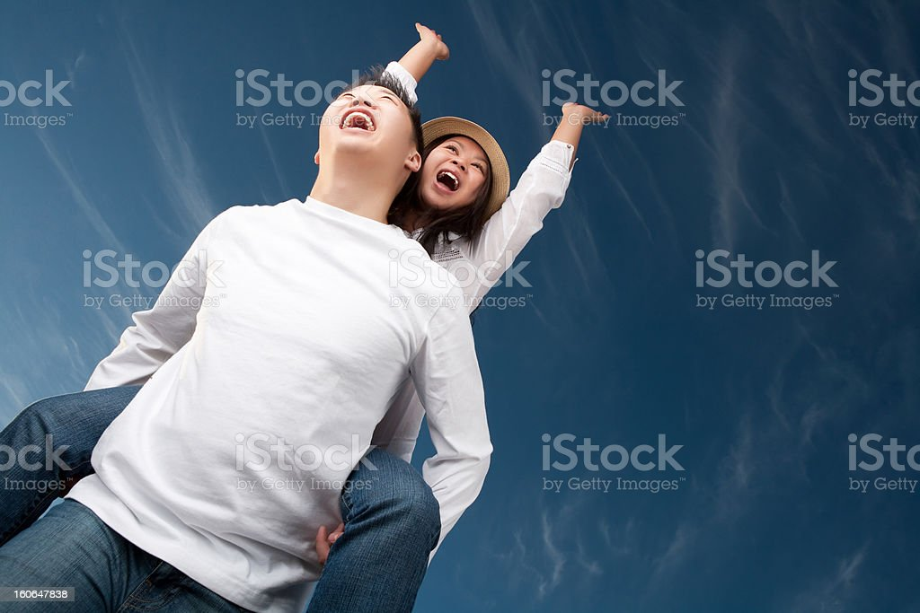 Excited asian couple with arms raised royalty-free stock photo