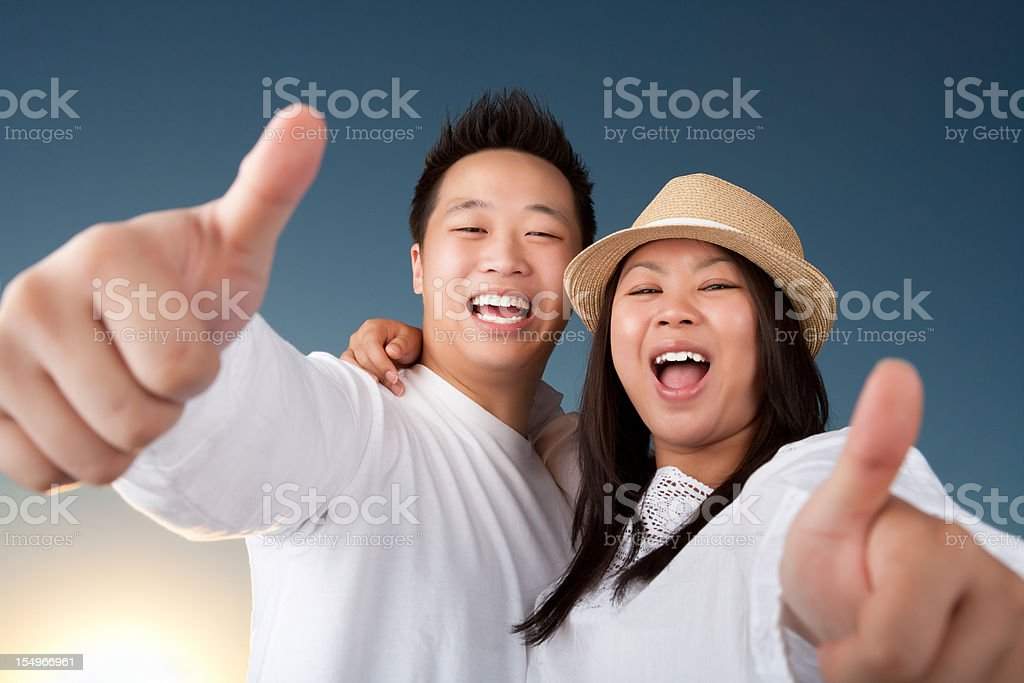 Excited asian couple with thumbs up royalty-free stock photo