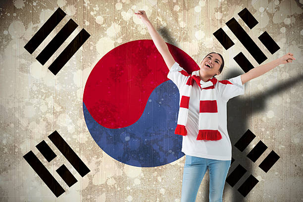 Excited asian football fan cheering Excited asian football fan cheering against south korea flag sopaatervinning stock pictures, royalty-free photos & images