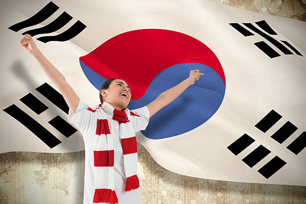 Excited asian football fan cheering Excited asian football fan cheering against korea republic flag sopaatervinning stock pictures, royalty-free photos & images
