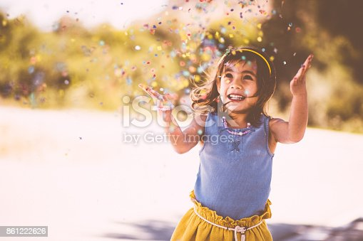 Cheerful little Asian female child having fun throwing confetti in the air at the park