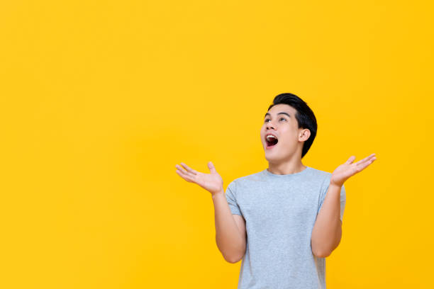 Excited Asian man gasping with hands open stock photo