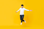 istock Excited asian man jumping over yellow background 1159293081