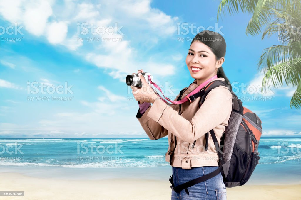 Excited asian tourist woman using camera to taking a photos - Royalty-free Adult Stock Photo