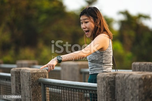 Excited young Asian woman indicates something below.